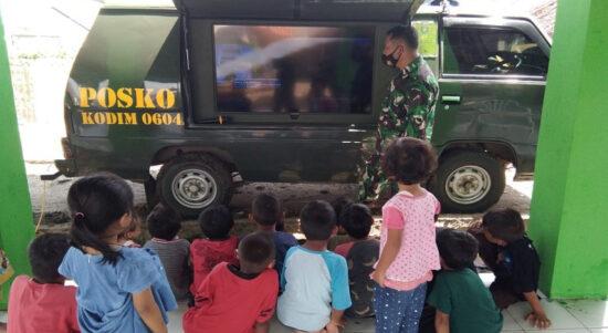 Anak -anak warga Kampung Tanjungsari menyaksikan siaran televisi yang ditayangkan dari failitas milik TNI. (Foto: iNews.id/Nilakusuma)